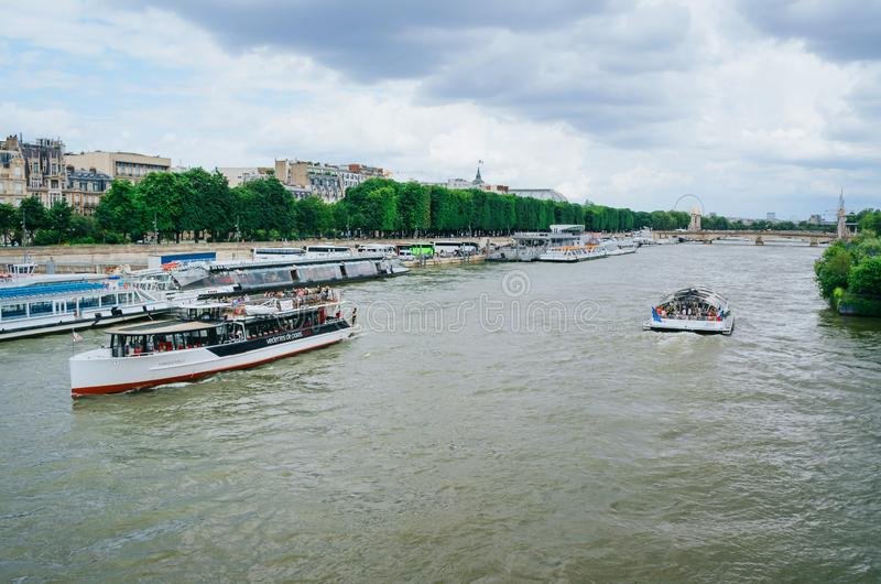 PARIS, FRANÇA - 26 DE JUNHO DE 2016: Navios de cruzeiros da excursão da cidade do turista em Seine River no dia de verão nebuloso imagem de stock royalty free