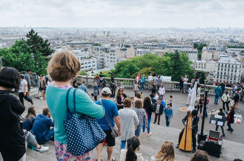 PARIS, FRANÇA - 26 DE JUNHO DE 2016: Turistas perto da catedral de Sacre Ceour de Montmartre Vista da cidade do ponto de vista do fotografia de stock royalty free