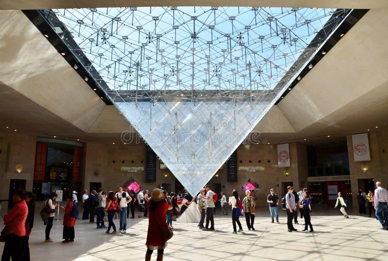 Paris, França - 13 de maio de 2015: Os turistas visitam dentro da pirâmide das grelhas imagens de stock royalty free