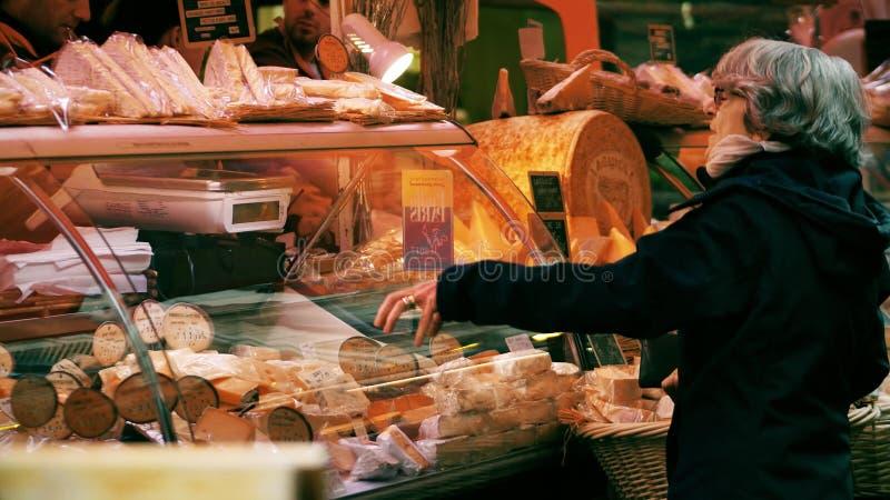 PARIS, FRANÇA - 7 DE OUTUBRO DE 2017 Cliente fêmea superior na tenda do queijo no mercado local do alimento imagem de stock royalty free