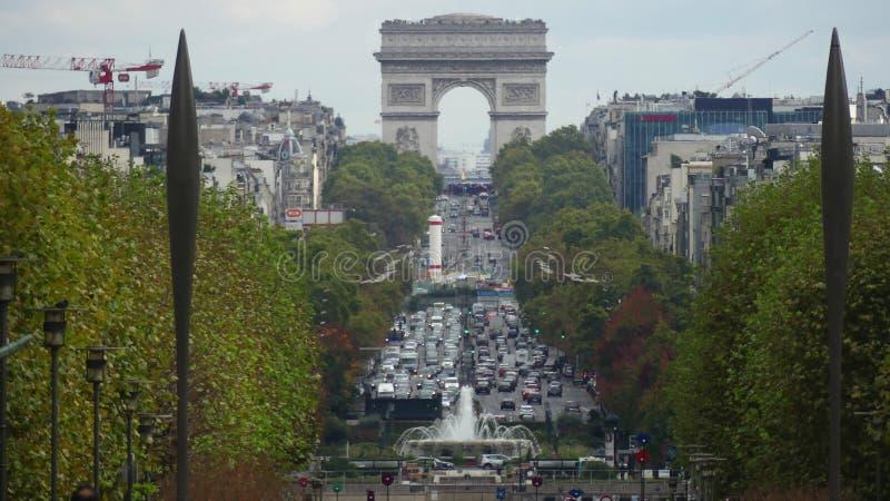 PARIS, FRANÇA - 8 DE OUTUBRO DE 2017 Tráfego de carro perto de Arc de Triomphe famoso ou do arco triunfal, tiro da lente teleobje fotografia de stock royalty free