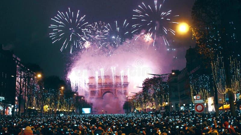 PARIS, FRANÇA - DEZEMBRO, 31 Fogos-de-artifício tradicionais do ano novo acima do arco triunfal famoso, Arc de Triomphe turistas imagens de stock royalty free