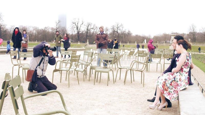 PARIS, FRANÇA - DEZEMBRO, 31, 2016 Fotógrafo asiático do casamento no trabalho Pares chineses que levantam no parque parisiense fotografia de stock royalty free