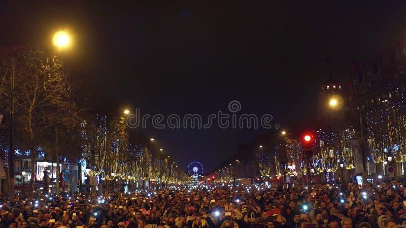 PARIS, FRANÇA - DEZEMBRO, 31 Povos que fazem fotos de fogos-de-artifício tradicionais do ano novo acima do arco triunfal famoso,  fotos de stock