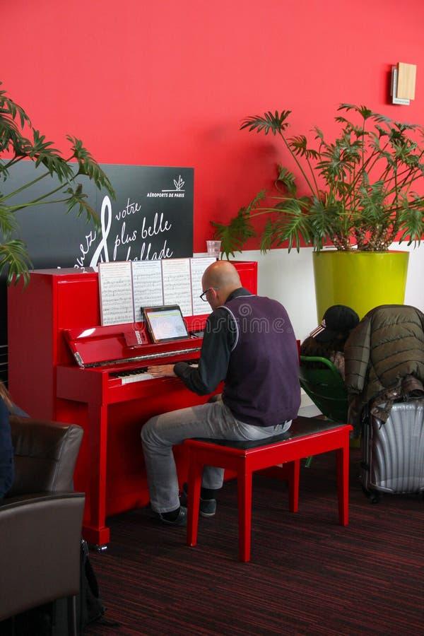 Paris, França - em abril de 2016: Homem calvo nos vidros que jogam o piano vermelho em uma sala de estar Charles de Gaulle Airpor imagens de stock royalty free