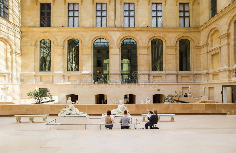 Paris/Fran?a - 4 de abril de 2019 Esculturas antigas no salão interno do museu do Louvre com povos do desenho fotos de stock royalty free