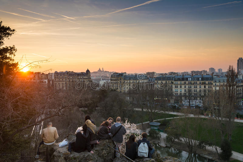 PARIS, FRANCE – MARCH 06, 2014: People enjoying the popular vi. Ew of Montmartre at sunset from les Buttes Chaumont park royalty free stock photography