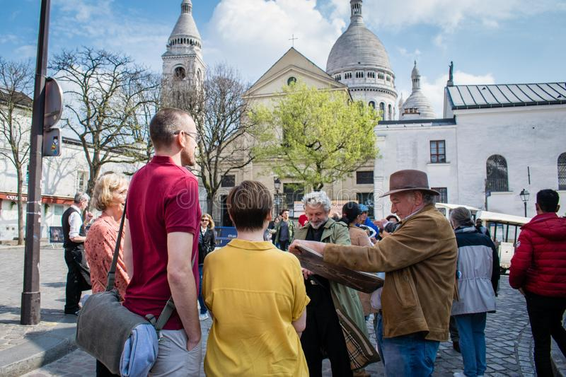 Paris, France - April 2, 2019 : Local painters sketching the portrait of tourists in Montmartre stock images