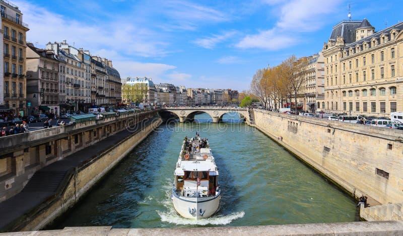 Paris / France - April 5, 2019: Beautiful cityscape of Paris, Saint-Michel bridge across Seine river and a tourist ship with touri stock photo