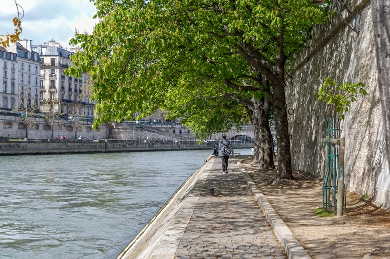 Paris, France, April 1, 2017: Quay at the edge of the canal with walkers. Geode in the background. Villette Park. Tourists walking near by Pont Neuf. The royalty free stock photography