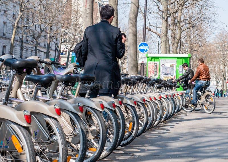 Paris, France - April 02, 2009: Young man depositing his bike at royalty free stock photo