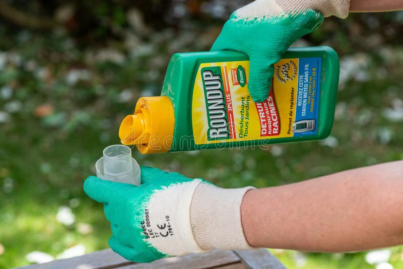 Paris, France - August 15, 2018 : Gardener using Roundup herbicide in a french garden. Roundup is a brand-name of an herbicide con. Taining glyphosate, made by royalty free stock photos