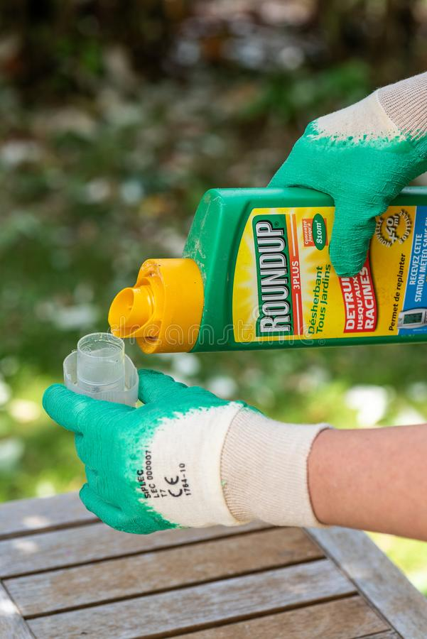Paris, France - August 15, 2018 : Gardener using Roundup herbicide in a french garden. Roundup is a brand-name of an herbicide con. Taining glyphosate, made by stock photos