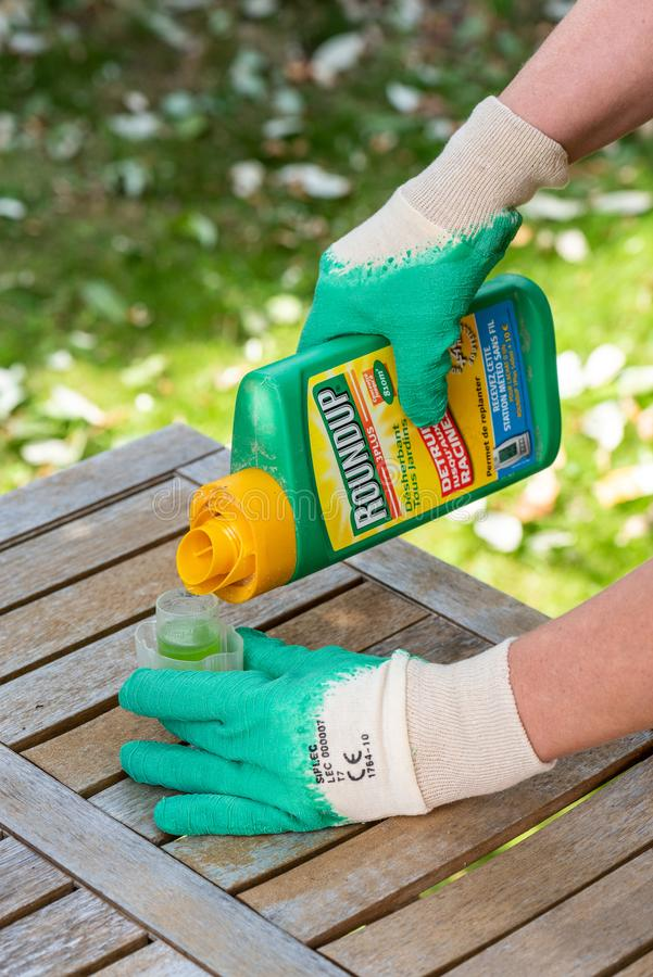 Paris, France - August 15, 2018 : Gardener using Roundup herbicide in a french garden. Roundup is a brand-name of an herbicide con. Taining glyphosate, made by stock photography
