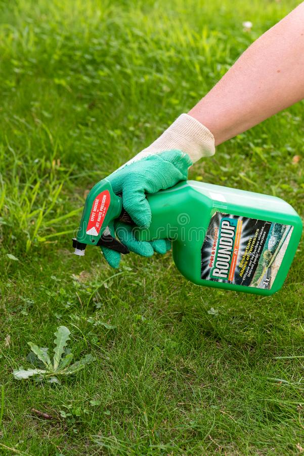 Paris, France - August 15, 2018 : Gardener using Roundup herbicide in a french garden. Roundup is a brand-name of an herbicide con. Taining glyphosate, made by stock image