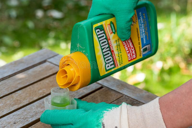 Paris, France - August 15, 2018 : Gardener using Roundup herbicide in a french garden. Roundup is a brand-name of an herbicide con. Taining glyphosate, made by royalty free stock image