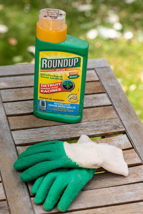 Paris, France - August 15, 2018 : Herbicide on a wooden table in a french garden. Roundup is a brand-name of an herbicide containi. Ng glyphosate, made by royalty free stock images