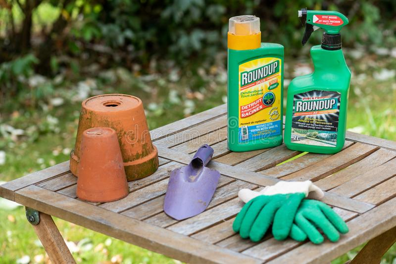 Paris, France - August 15, 2018 : Herbicide on a wooden table in a french garden. Roundup is a brand-name of an herbicide containi. Ng glyphosate, made by stock images