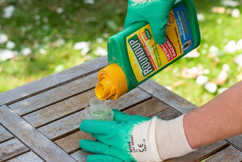 Paris, France - August 15, 2018 : Herbicide on a wooden table in a french garden. Roundup is a brand-name of an herbicide containi. Ng glyphosate, made by stock photo