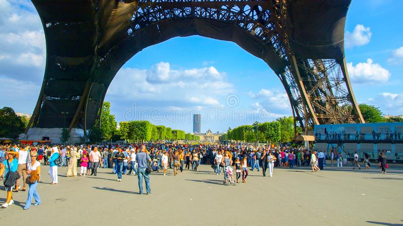 PARIS, FRANCE - AUGUST 8, 2010: Many tourists under Eiffel tower on sunny summer day. Paris, France. royalty free stock photo