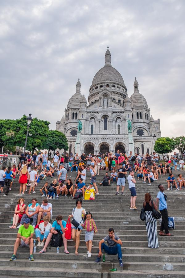 Tourists on the steps to the church of Sacre-Coeur in Montmartre in Paris, France on a hot even if cloudy summer afternoon. royalty free stock photo