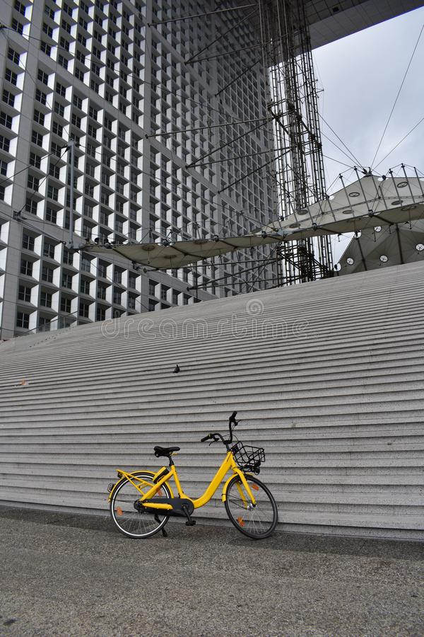 Paris, France Bicyclette jaune dans le Grande Arche District des affaires de la défense de La Jour pluvieux image libre de droits