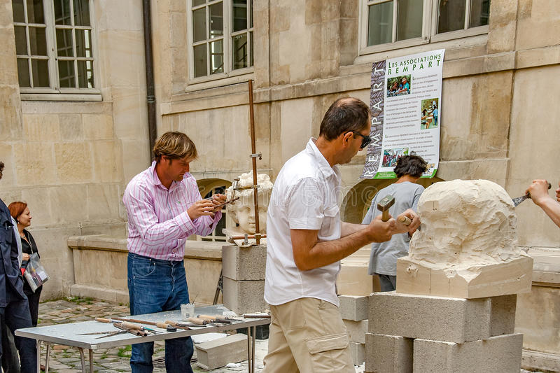 PARIS, FRANCE. Circa april 2016. Exhibition of artisans stone sculptor. Of the association rempart making a sculpture in stone in Paris royalty free stock images