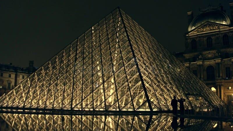 PARIS, FRANCE - DÉCEMBRE, 31, 2016 Couplez les silhouettes près de la pyramide en verre de Louvre la nuit Musée français célèbre  photos stock