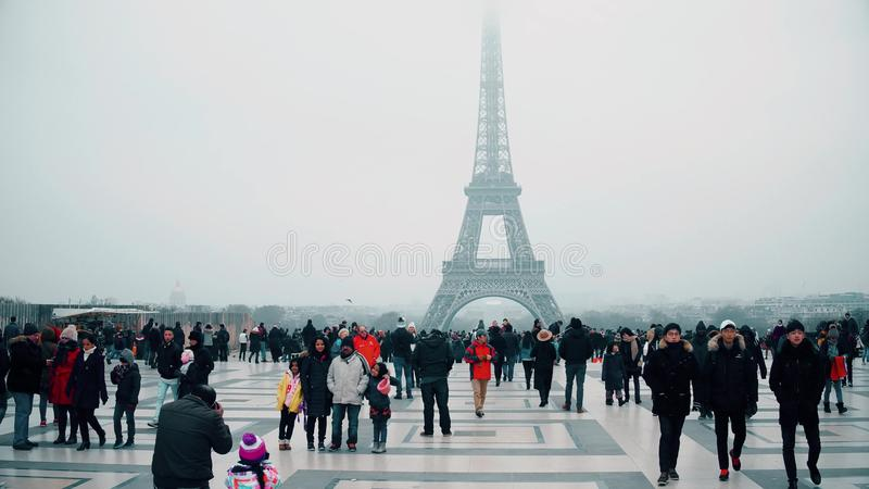 PARIS, FRANCE - DECEMBER, 31. Multinatonal tourists taking photos and making selfie near Eiffel Tower, the most famous stock photography