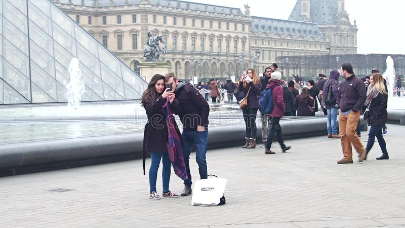 PARIS, FRANCE - DECEMBER, 31, 2016. Steadicam shot of couple making selfie near the Louvre glass pyramid and fountains royalty free stock photo