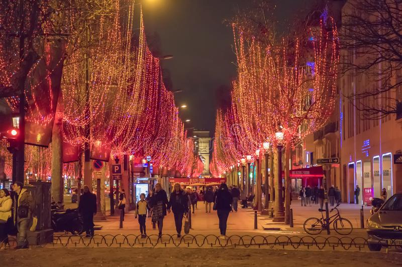 Street view at the Triumphal Arch and Champs Elysees avenue illuminated for Christmas stock photos
