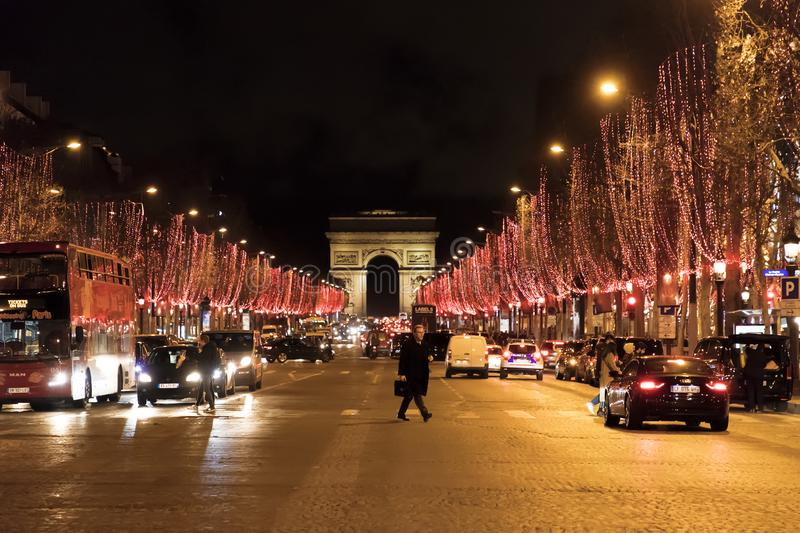 Street view at the Triumphal Arch and Champs Elysees avenue illuminated for Christmas royalty free stock image