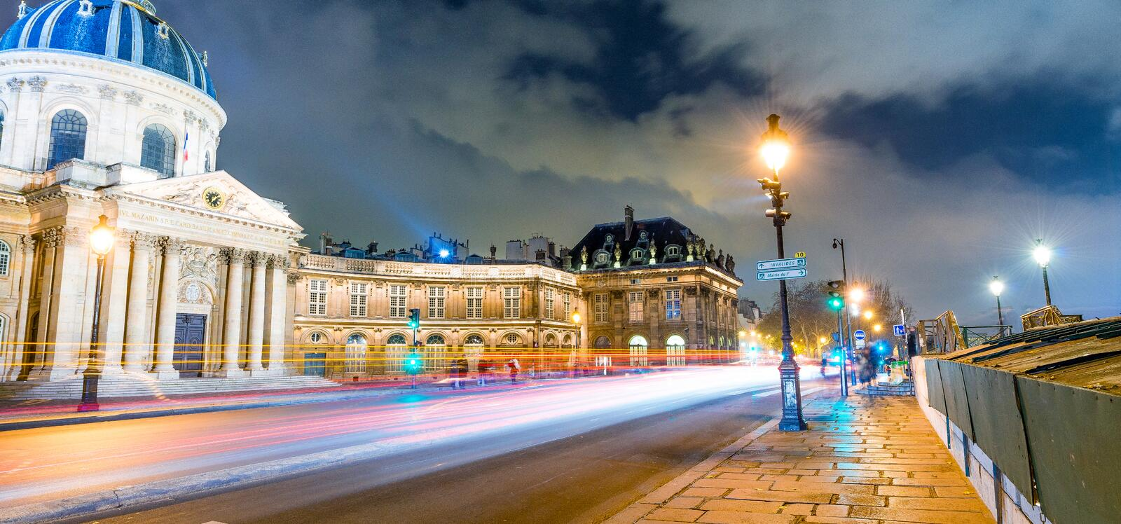 PARIS, FRANCE - DECEMBER 2012: Traffic light trails on city streets at night. The city attracts 40 million people every year stock image
