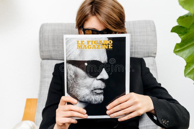 Woman reading Le Figaro magazine newspaper about Karl Lagerfeld death royalty free stock images