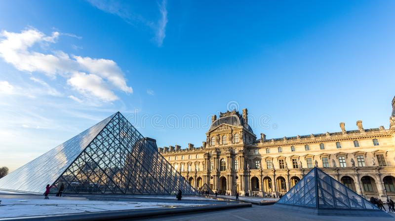 PARIS, FRANCE. Feb 2018: Louvre Museum view at sunset, with the glass of the pyramid reflecting clouds. royalty free stock images