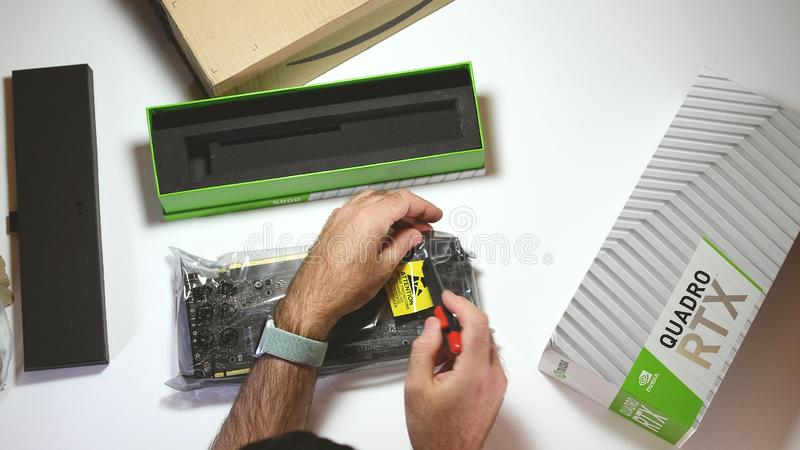 Above view unboxing of Nvidia Quadro RTX 5000 GPU. Paris, France - Feb 20, 2019: View from above POV man unboxing latest Nvidia Quadro RTX 5000 workstation royalty free stock images