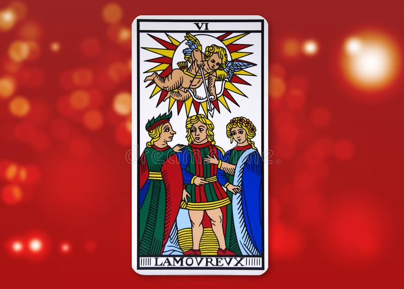Paris, France - February 18, 2018 : Tarot Card - The Lovers. Tarot of Marseille on red blurry background stock images