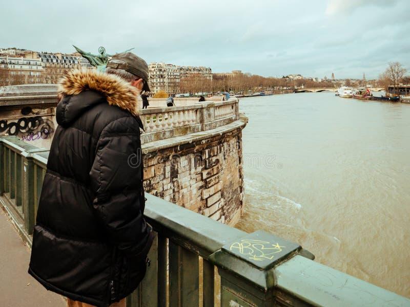 Parisian French man watching the flooding swollen Seine river. PARIS, FRANCE - JAN 30, 2018: Parisian senior man watch the swollen river Seine near the Eiffel stock photography
