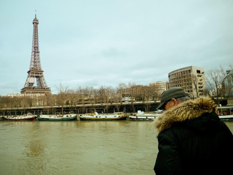 Parisian French man watching the flooding swollen Seine river. PARIS, FRANCE - JAN 30, 2018: Parisian senior man watch the swollen river Seine near the Eiffel royalty free stock images