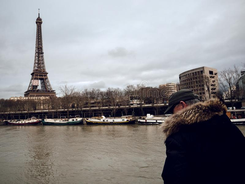 Parisian French man watching the flooding swollen Seine river. PARIS, FRANCE - JAN 30, 2018: Parisian senior man watch the swollen river Seine near the Eiffel royalty free stock image