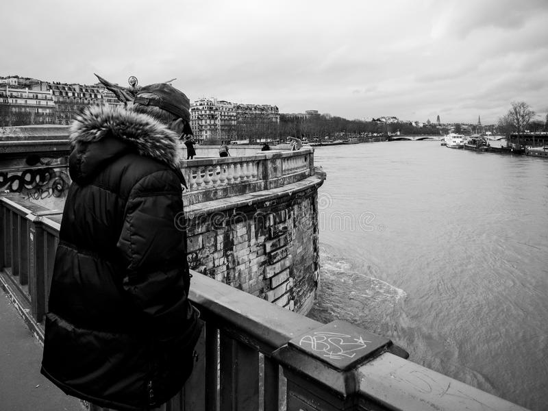 Parisian French man watching the flooding swollen Seine river. PARIS, FRANCE - JAN 30, 2018: Parisian senior man watch the swollen river Seine near the Eiffel stock photo