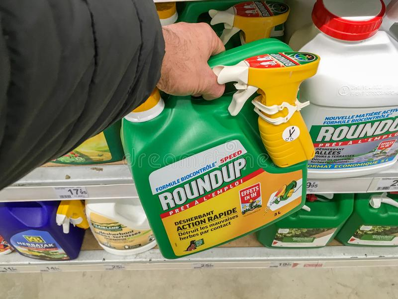 Paris, France - January 25, 2019: Customer buying roundup in a french Hypermarket. Roundup is a brand-name of an herbicide containing glyphosate, made by royalty free stock photos