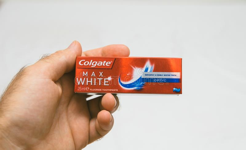 Man holding Colgate small ai travel format. PARIS, FRANCE - JUL 27, 2018: Man holding Colgate small air security rules conformed travel toothpaste against white stock photo