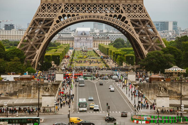 Paris, France July 24, 2017: Eiffel Tower close-up of a road with cars and buses traffic from a transporter, passage under an arch stock photography