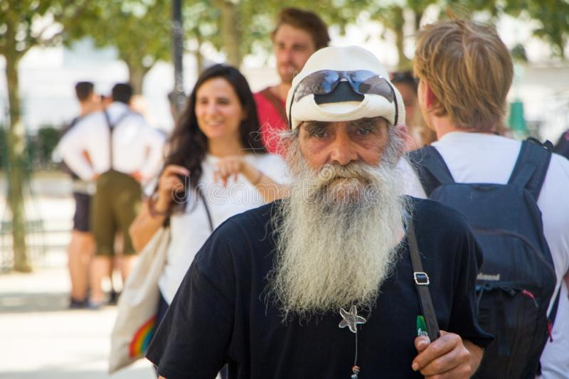 An elderly man in a cap and a gray long beard is walking, a tourist in Paris stock images