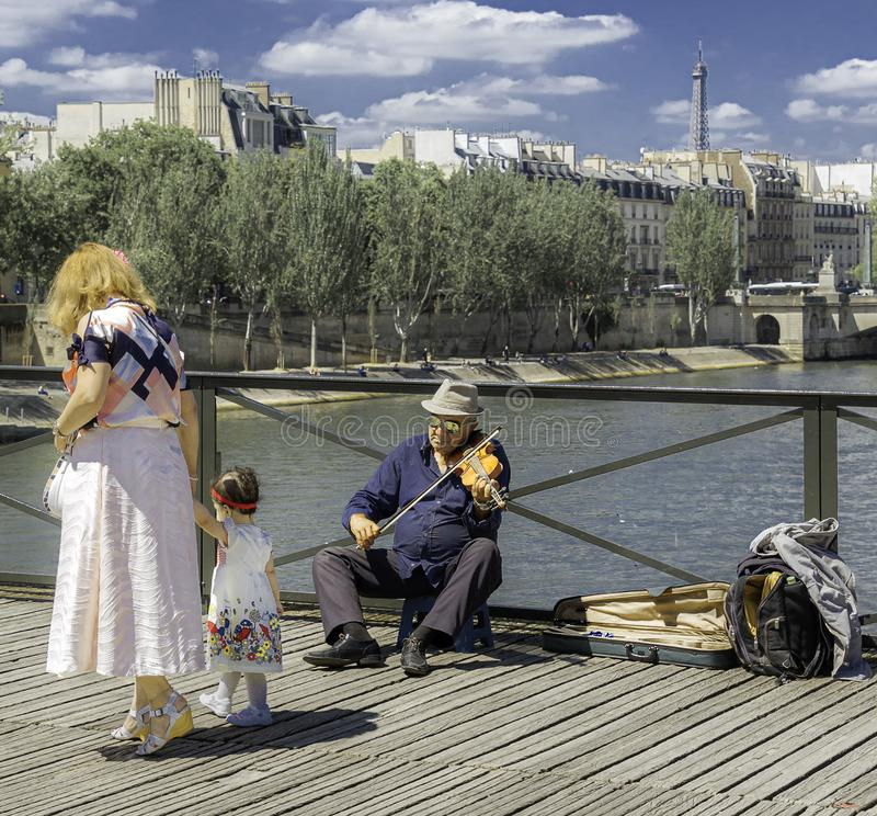 Old man playing violin at Pont des Arts - The Love Lock Bridge. Paris, France - July 4, 2017: Old man on a stool playing violin as tourists passing by for tips stock photos