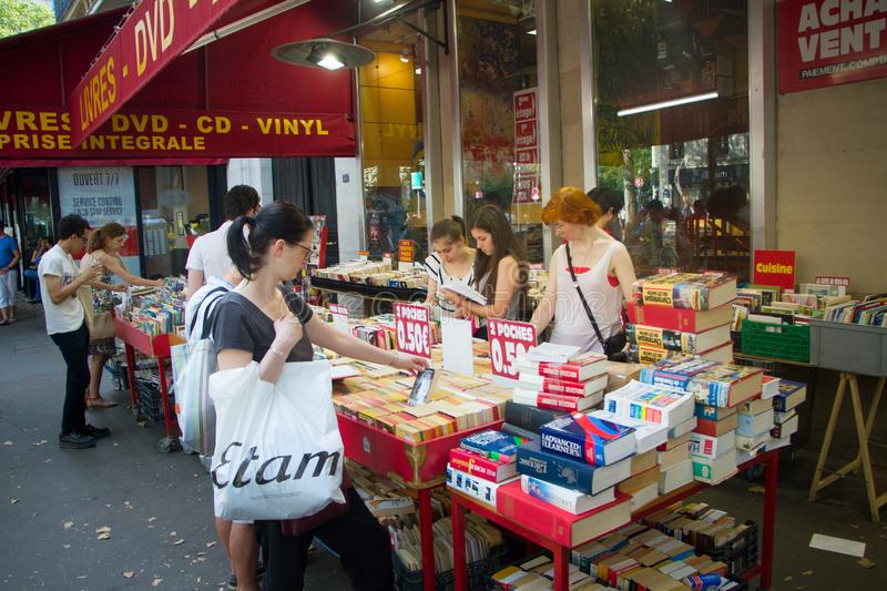 Street sale of new and used books on a street in the center of Paris, people choose books and CDs. Paris, France - July 7, 2018: Street sale of new and used stock image
