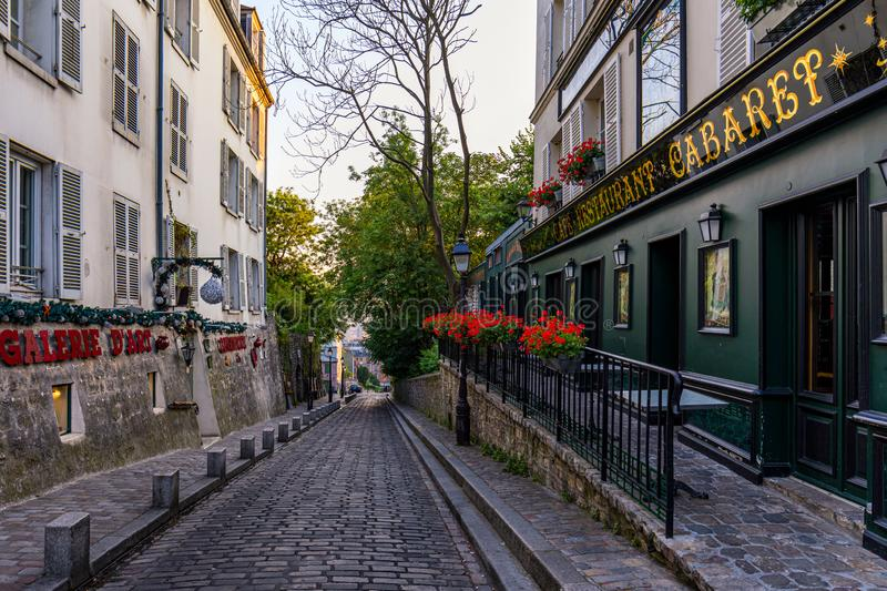 Paris, France - July 7, 2018: Street with tables of cafe in quarter Montmartre in Paris, France. Cozy cityscape of Paris. royalty free stock images
