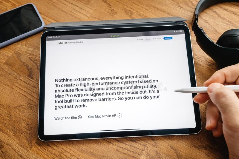 Man reading on iPad Pro launch Mac Pro workstation. Paris, France - Jun 6, 2019: Man reading on Apple iPad Pro tablet about latest announcement of at Developers stock image