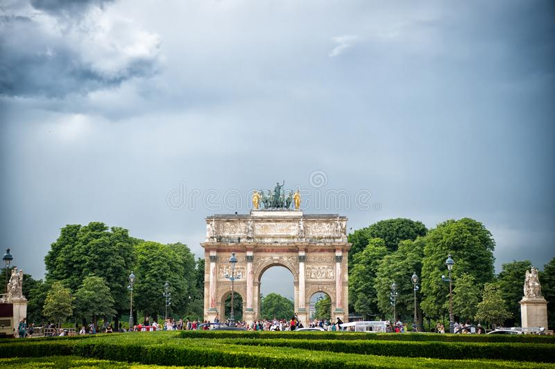 Paris, France - June 02, 2017: Arc de Triomphe du Carrousel in Louvre Palace. Arch monument and green trees on blue sky. Architect royalty free stock images